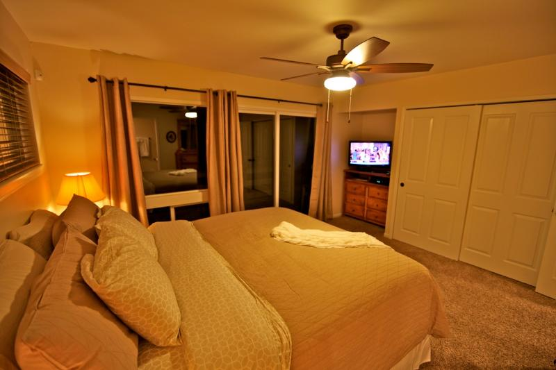 Master bedroom with ceiling fan and flat screen TV