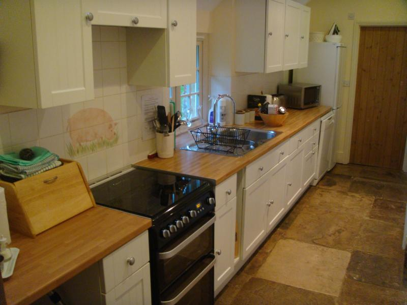 Galley kitchen leading to downstairs utility room.