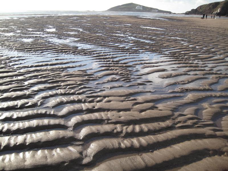 Acres of sand at Bantham at low tide with Burgh Island with its famous hotel on the horizon