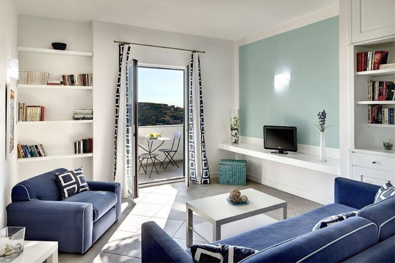 En la zona de estar de planta abierta, hay un sofá cama doble, dos sillones y televisión por satélite.