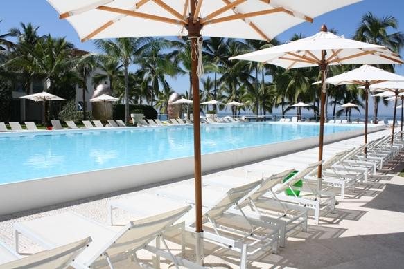 Umbrellas and lounge chairs by the pools , part of the amenities of the common areas in the complex