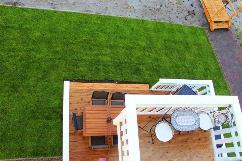 Blick von der Dachterrasse auf Balkon und Terrasse des Strandhaus Libelle und dessen Wiese