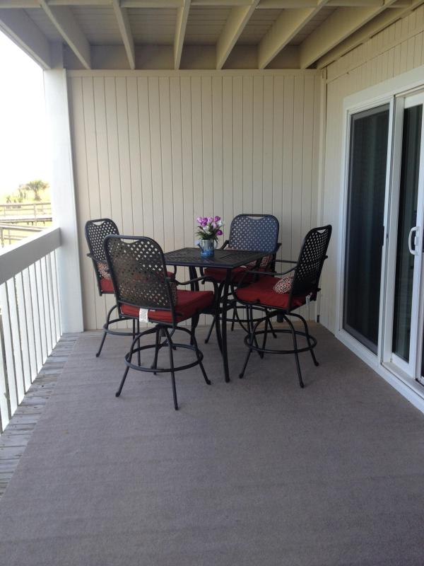 HIGH PUB DINING TABLE WITH SEATING FOR FOUR ON CARPETED BALCONY DECK
