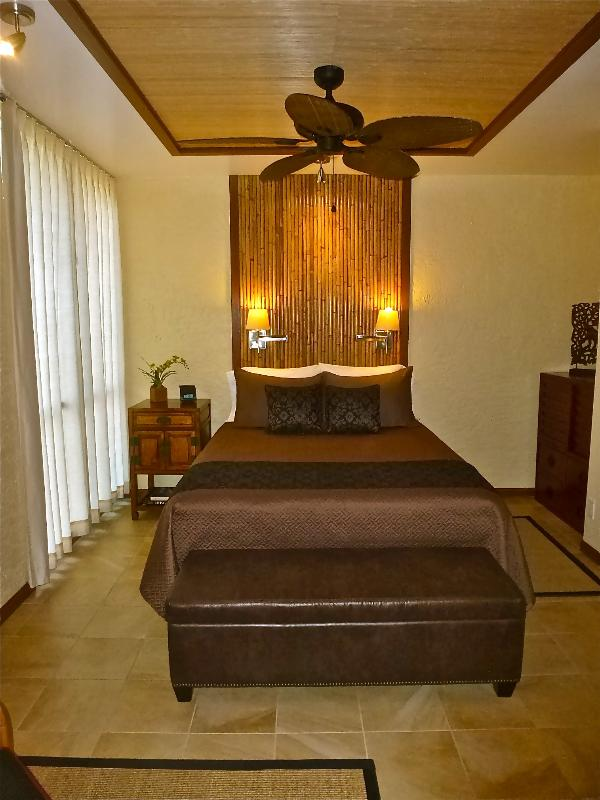 Amplio dormitorio con cabecero personalizado y caoba y recuadro de techo de bambú