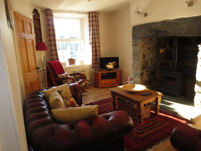 Cosy sitting room, with leather Chesterfield sofas, inglenook and user-friendly, gas-fired stove
