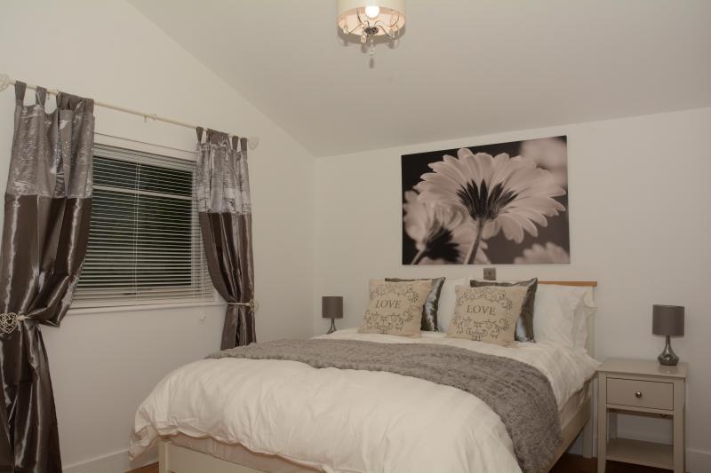 Schlafzimmer mit Doppelbett mit Bettwäsche aus ägyptischer Baumwolle und Ausblick auf Wald und koppeln