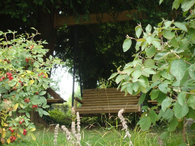 Schaukel hing von den Bäumen mit kleinen Holztischen in den Stämmen für Ihr Sektglas integriert