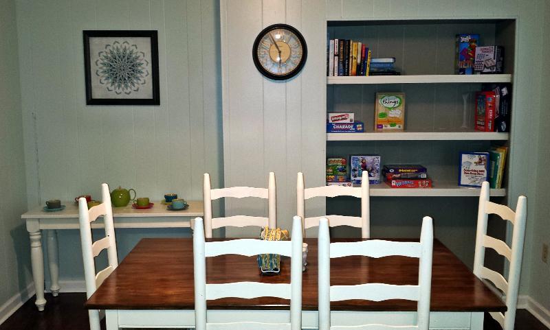 Comedor con estantes para libros, juegos y rompecabezas