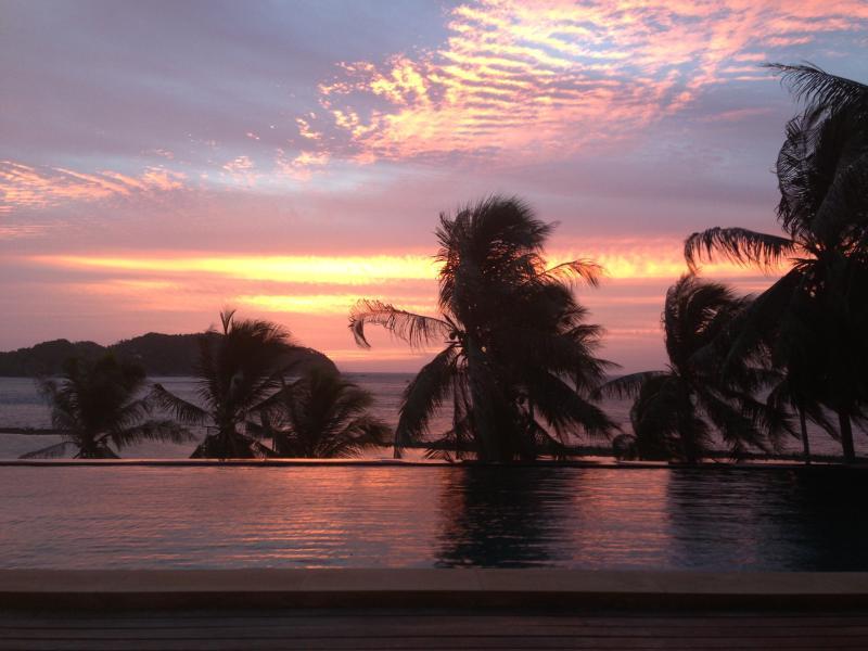 Nuestra increíble puesta de sol desde la terraza a través de la piscina infinita.