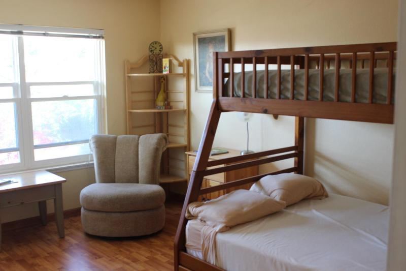 Second story bedroom with bunkbeds, double on bottom, single on top.