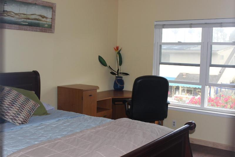 Guest room with queen bed on upper level with work station