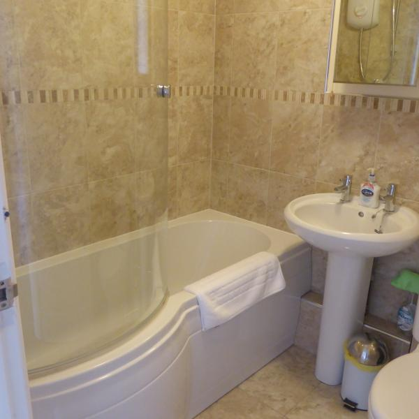 Fully tiled bathroom with electric shower over bath