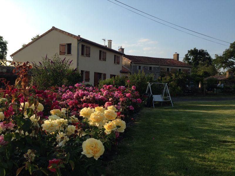 Casa rural y jardín de rosas.