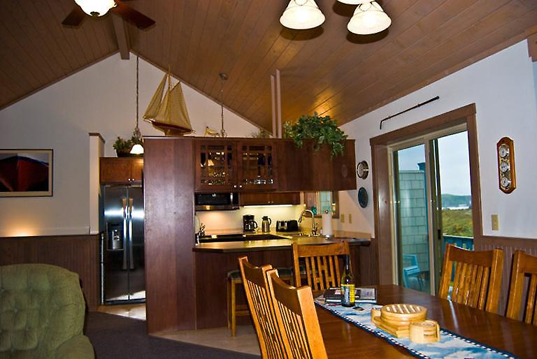 Pass thru kitchen with 3 bar stools and dining table for 8.