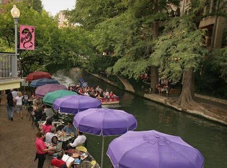 Pasear por el paseo del río San Antonio a restaurantes, tiendas, paseos en barco y el álamo