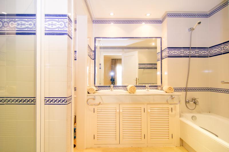 En suite bathroom with bathtub and separate shower
