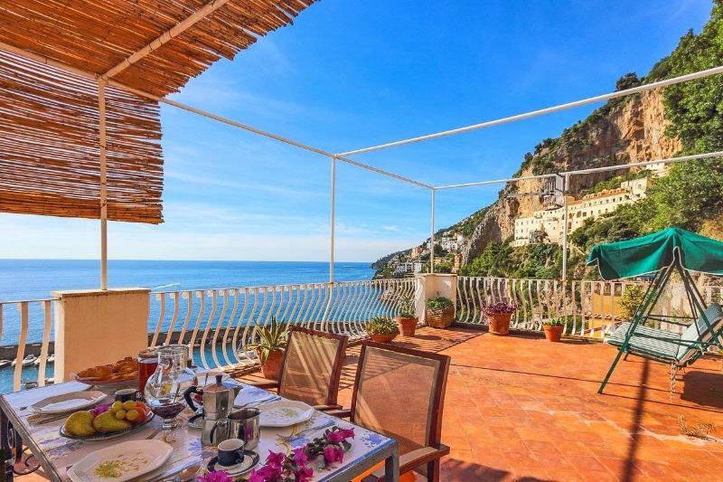 gran terraza equipada con mesa y sillas, barbacoa, 2 tumbonas y una mecedora.