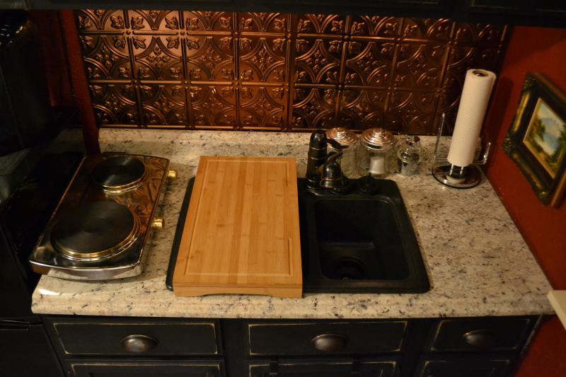 Kitchenette has large over-the-sink cutting board for more counter room. Two-top range works great!
