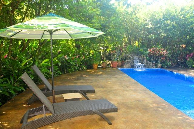 Private pool with lounge chairs & market umbrellas.