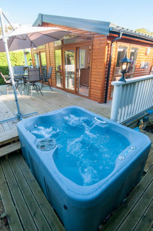 Private hot tub to rear of cabin, ready to jump into after alfresco lunch on veranda.