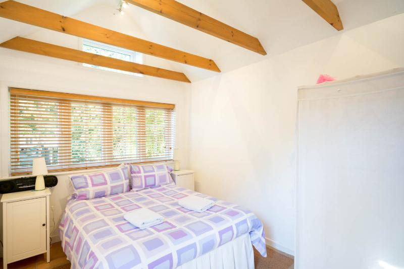 Annexe with double bed and open plan shower, basin and wc.
