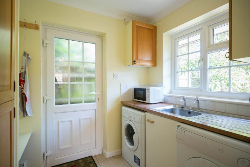 Utility room with washing machine and tumble dryer.