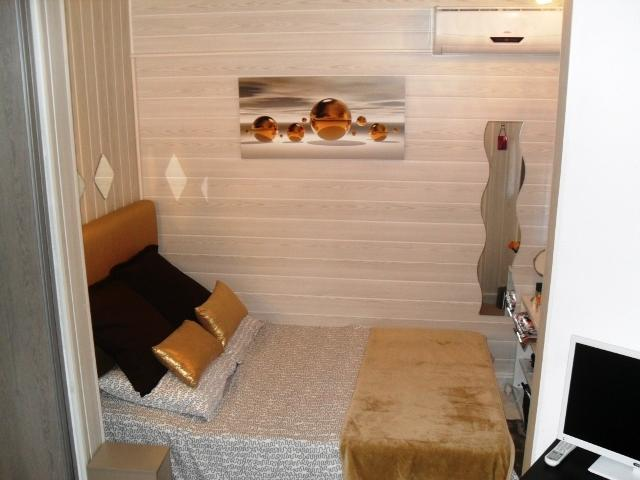 Modern bedroom area, bed made up ready for arrival. Make up area with hairdryer and mirrors.
