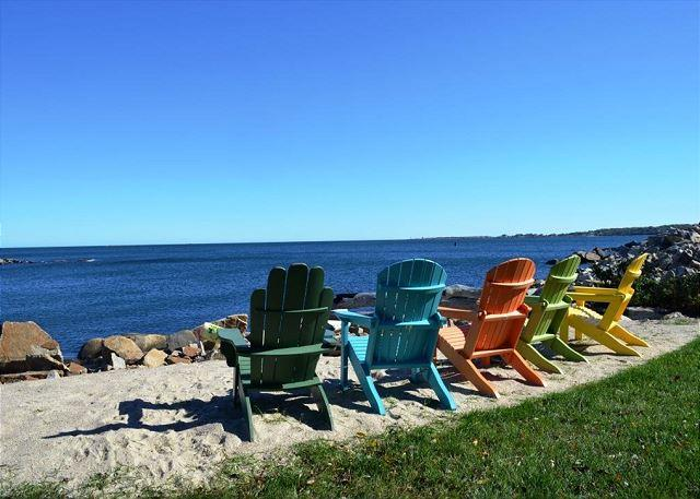 A waterfront fire pit and colorful chairs make sitting by the wa