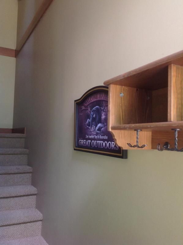 Shelf with cubby holes at entrance with a 'Bearadise - Welcome to the Great Outdoors' print