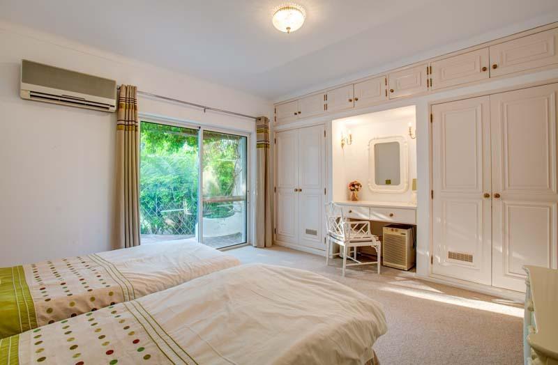 Dormitorio doble con puertas correderas en cristal con acceso y vistas sobre el patio soleado