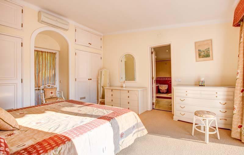 Spacieuse chambre des maîtres avec portes coulissantes en verre avec accès et vue sur la terrasse supérieure