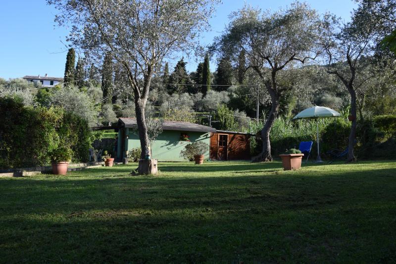 giardino attrezzato con lettini, ombrellone e doccia acqua calda