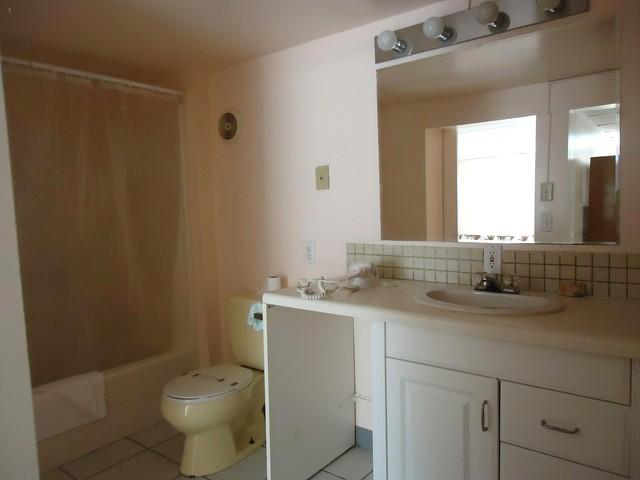 bathroom with tub/shower, sink with vanity mirror