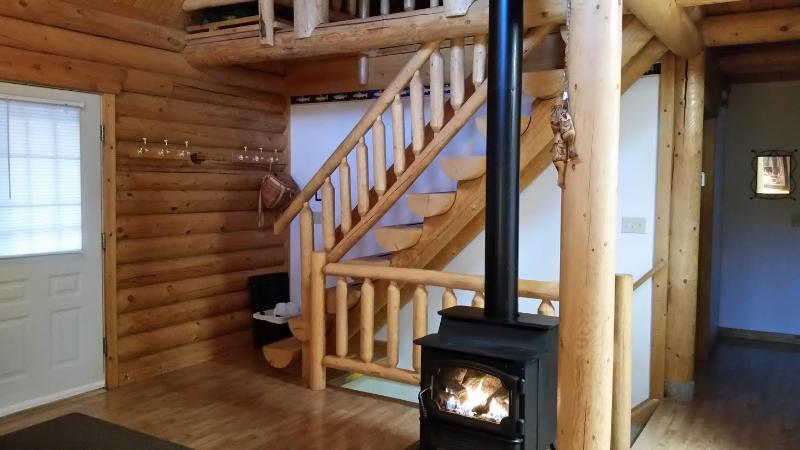 The gas fired wood stove and stairs leading to loft at the Log Cabin