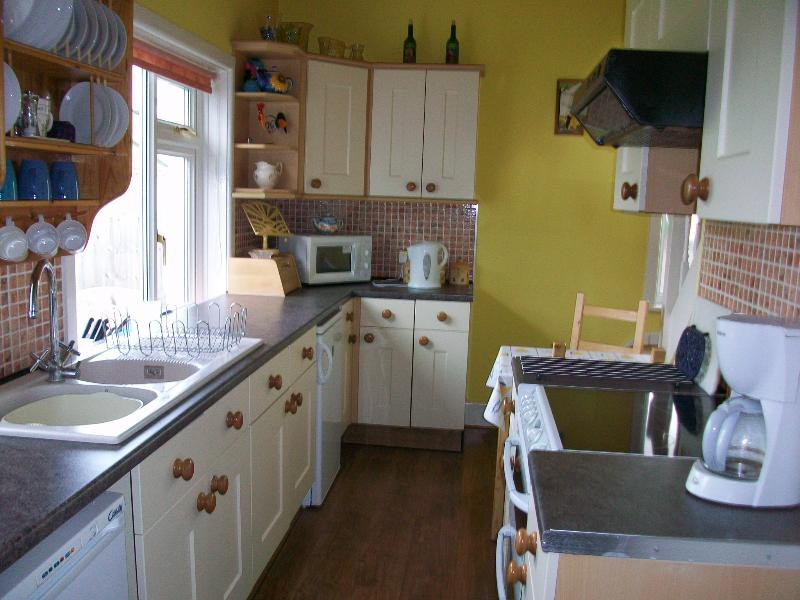 well equipped kitchen with small table/chairs and stairs to master bedroom