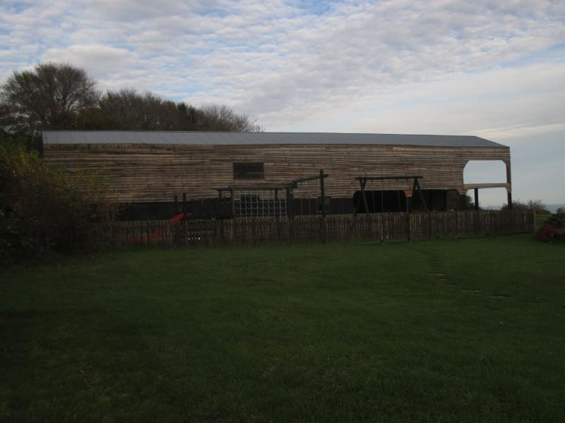 Play area with barn, containing cider press and viewing area, behind