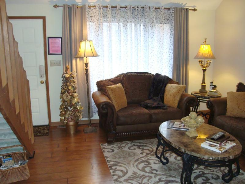 Puerta de entrada de la sala de estar & pared de ventanas; elegante asiento de amor. A la derecha es la puerta de entrada.