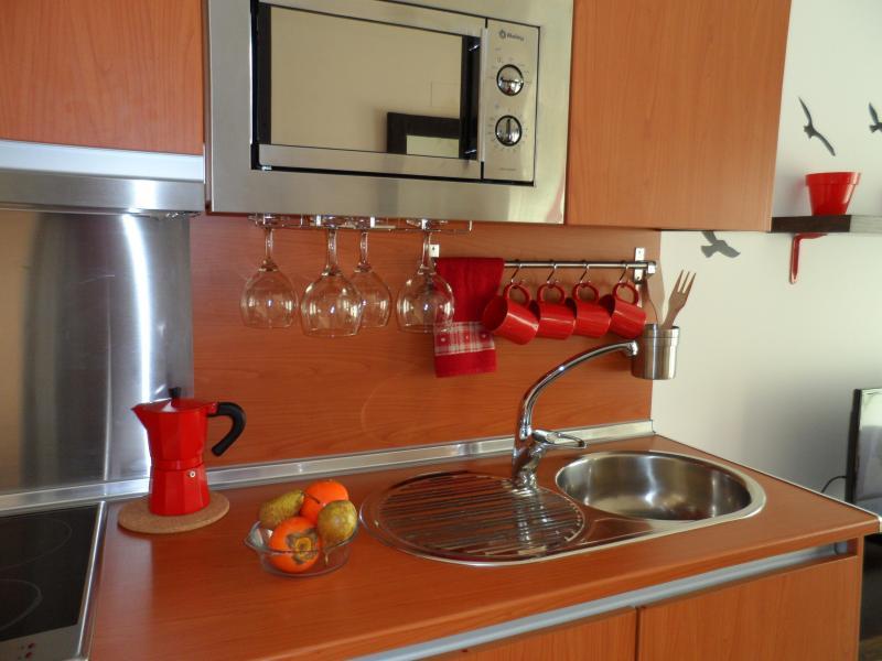 Zona de cocina, detalle de microondas y copas, tazas cafetera...etc