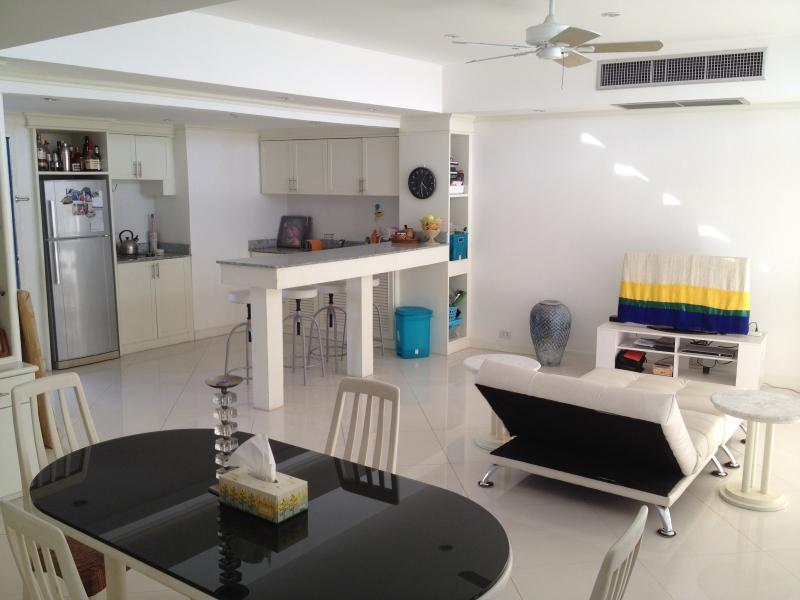 Cool, all-white, open-plan living room, kitchenette, bar area.