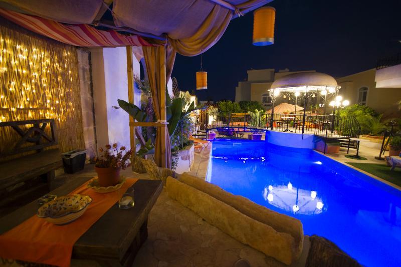 Chill out área durante a noite, com vista para a área de churrasco e Gazebo iluminado