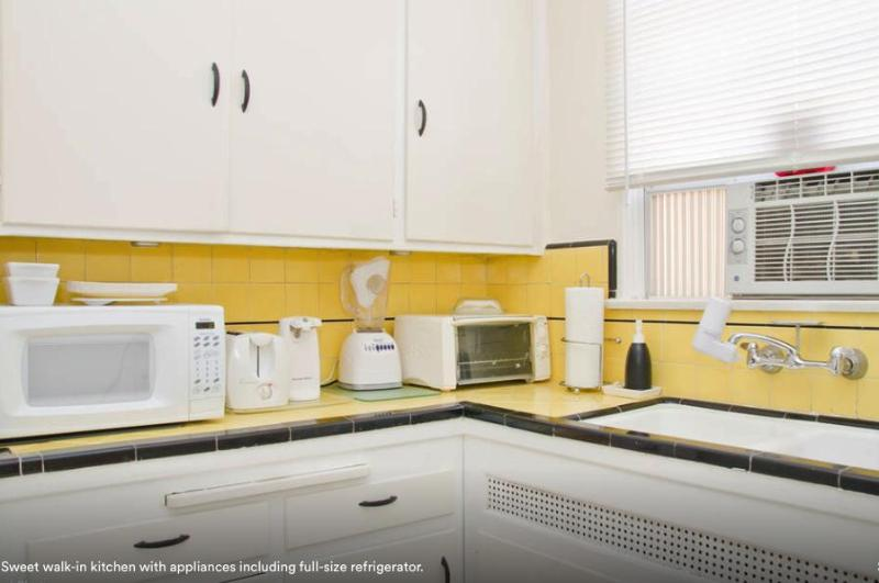 Sweet walk-in kitchen with appliances including full-size refrigerator.