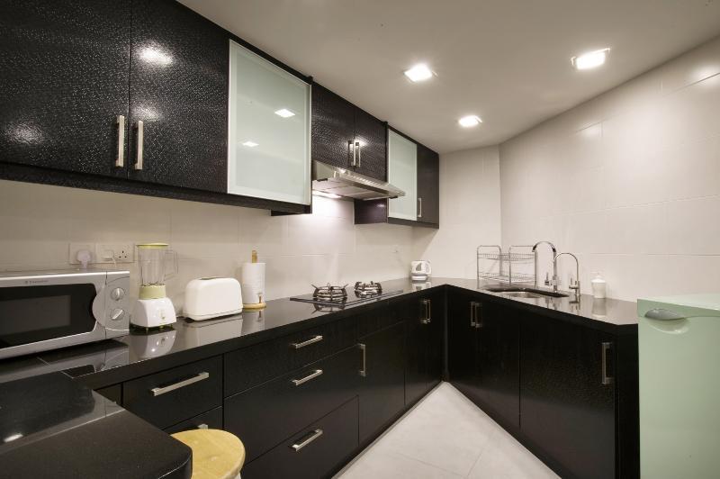 Cucina con armadi lucido e piani in granito nero