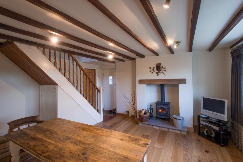 Dining room with exposed beams, wood burning stove, and underfloor heating...