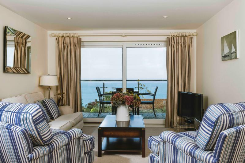 Open plan living, dining and kitchen area with door to private balcony with seaviews