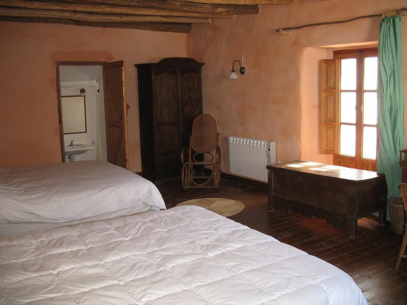 habitacione con dos camas doble y un cuarto de bano privado
