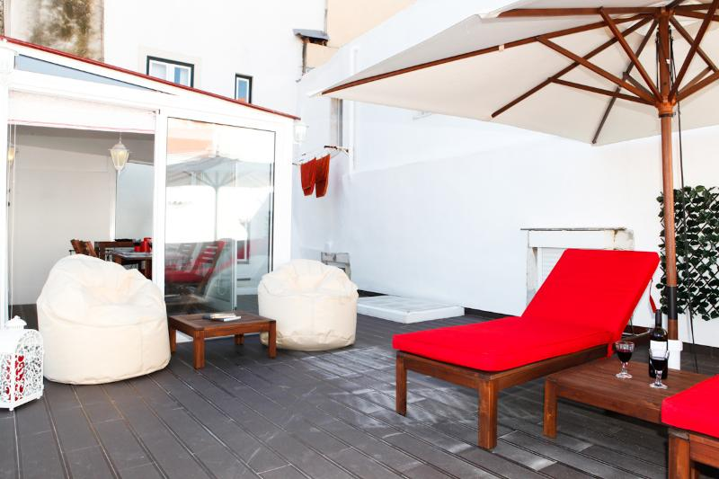 Comfortable terrace with a parasol, two sun loungers and two puffs