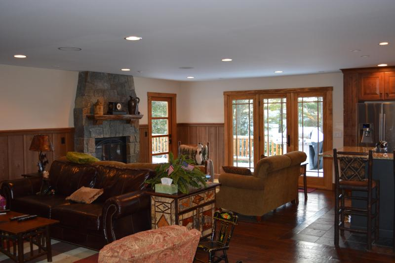 A view of the large great room, includes kitchen, dining area, TV area, and fireplace area.