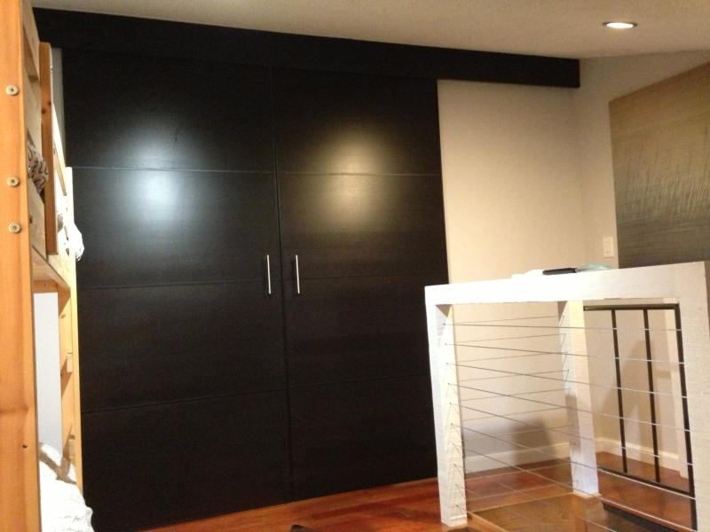 Espresso sliding doors divide sleeping loft and master suite