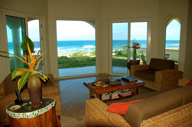 En la planta baja área con vista al mar y tres puertas corredizas de vidrio que viven acceder a la playa