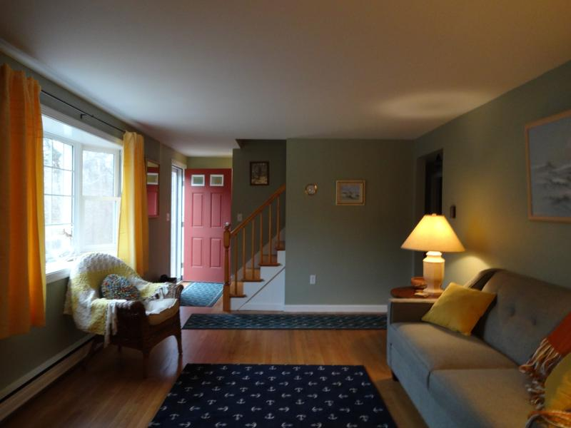 comfortable, bright living room with TV. Hardwood floors throughtout